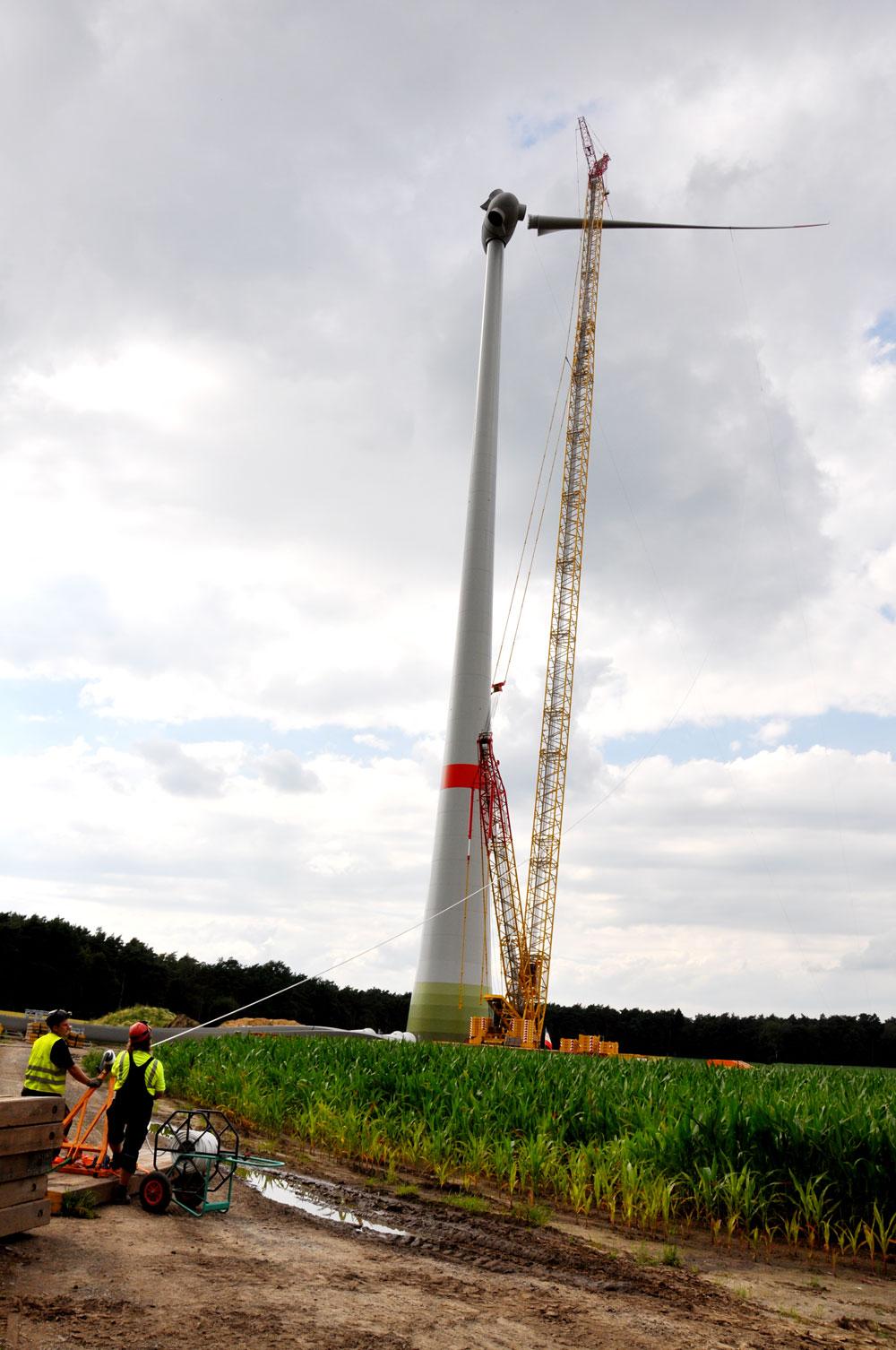 Montage der 56 m langen Rotorblätter an die Nabe des Turms in 149 m Höhe.